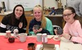 female students enjoy hot chocolate out of mugs they created