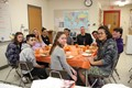 students and staff at table smiling