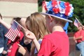 Boy with patriotic hat waving small American flag at Port Dickinson Flag Day event
