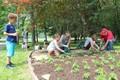 students help plant flowers in Port Dickinson Community Park garden
