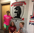 students standing in front of c v mural