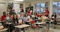students holding up clocks