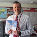 teacher holding pamphlet