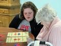 student helping elizabeth church manor resident with bingo