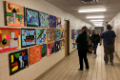 people looking at student artwork