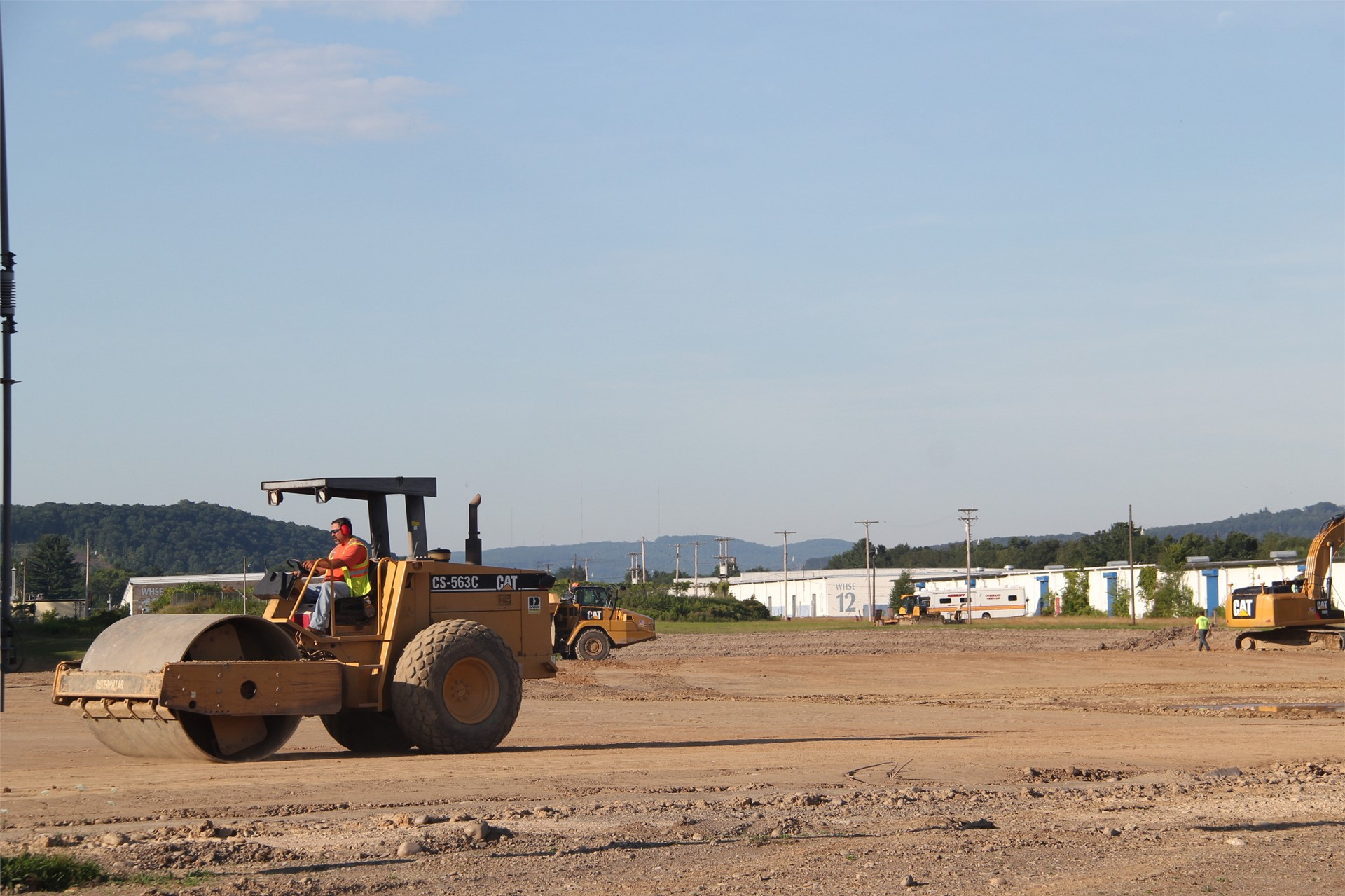 wide shot of construction scene outdoors with person working in machine