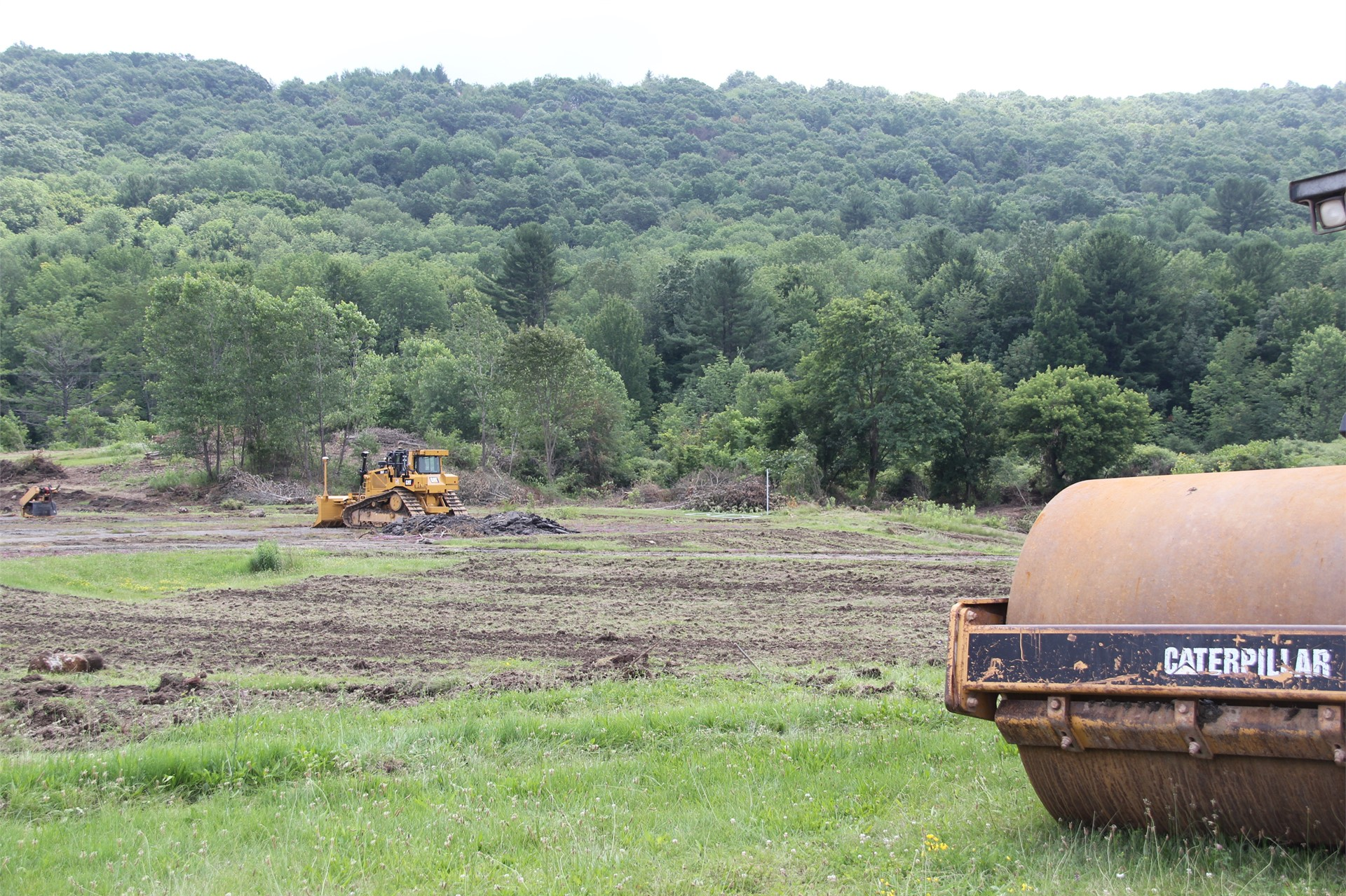 wide shot of construction scene with wooded area behind it