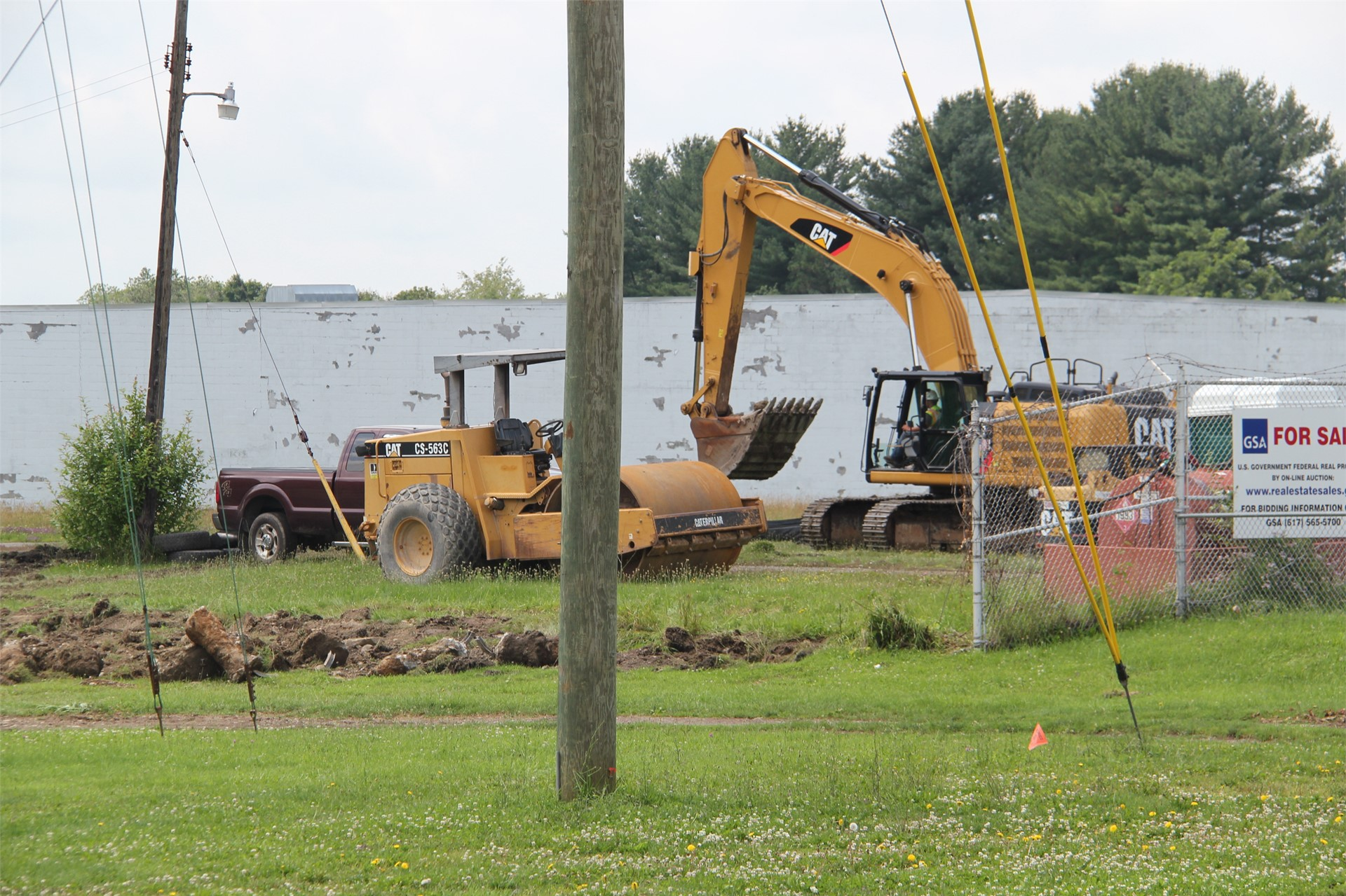far shot of person inside equipment working on construction outdoors