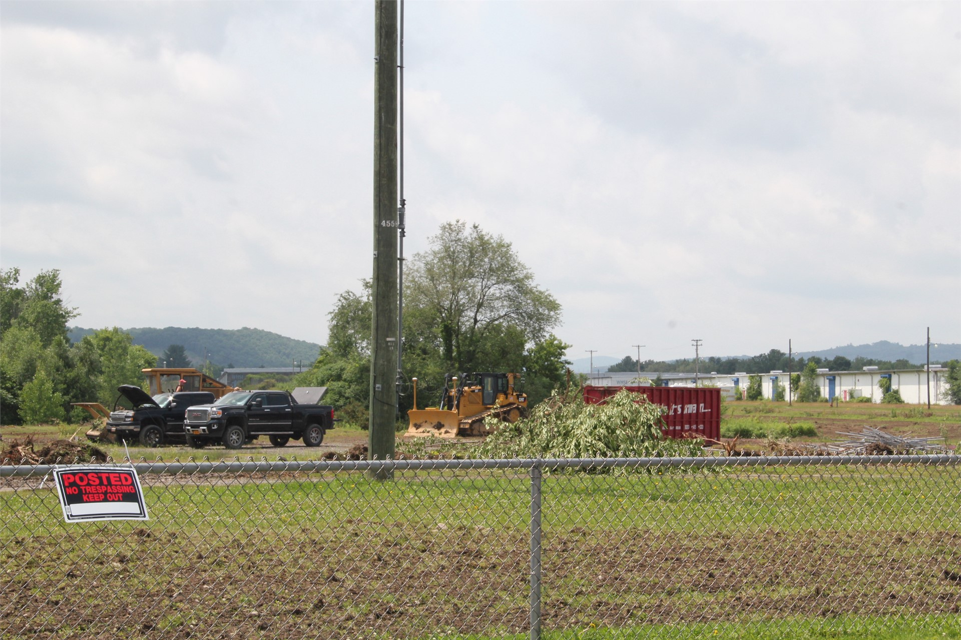 far shot of trucks and equipment at construction scene outdoors