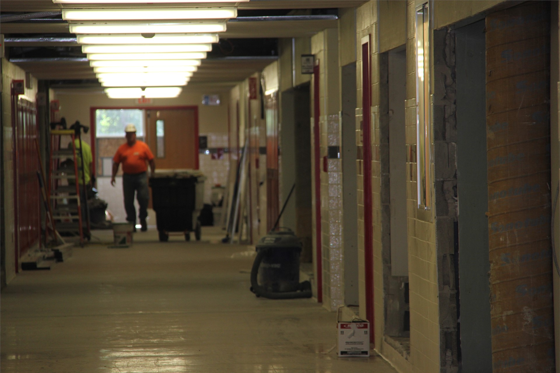 far shot of people working on construction in hallway