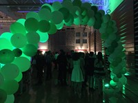 green arch welcoming students into homecoming dance