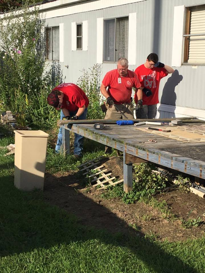 c v students and ramp it up coordinator continue work on removing old boards from deck.