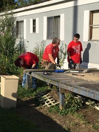 c v students and ramp it up coordinator work on removing old boards from deck