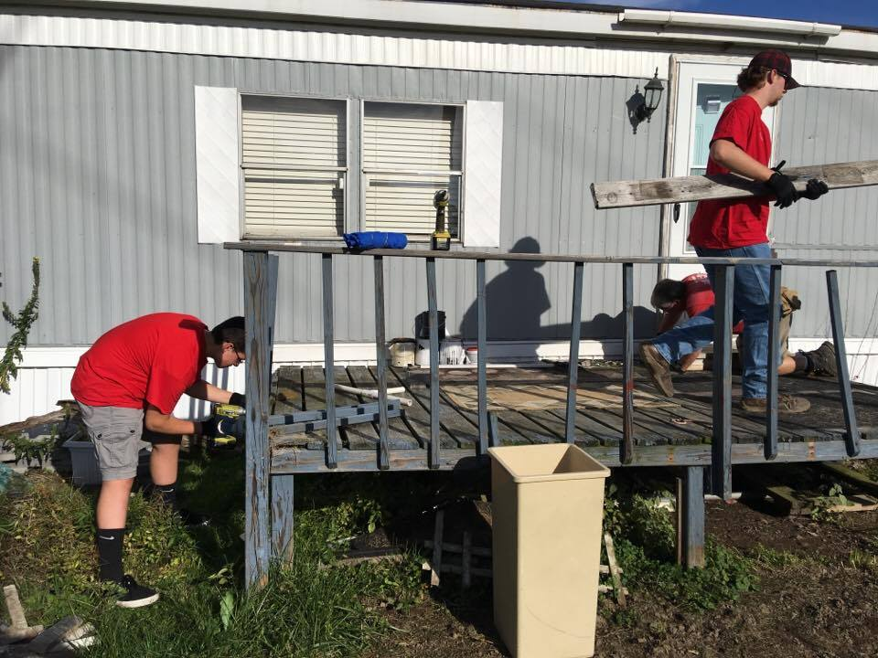 chenango valley students remove old boards from deck to begin new construction for ramp it up projec