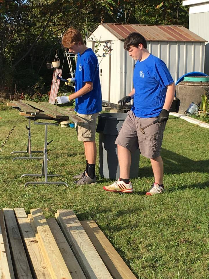 two students work on hammering nails in preparation for ramp it up project