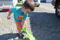 Little boy helps shovel at ramp it up project