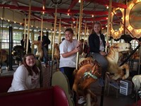 more students smiling riding carousel