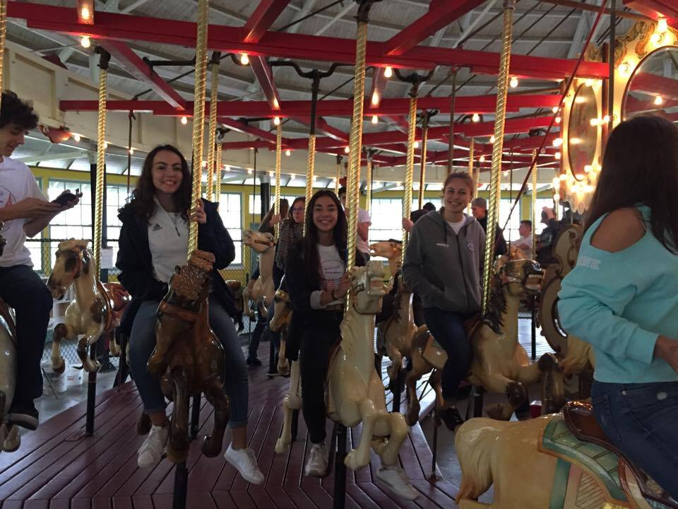 students smiling riding carousel