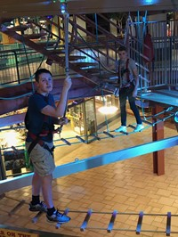 two male students on a rope course at destiny u s a mall
