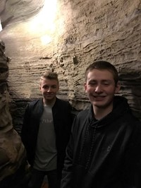 students smile for picture inside of rock structure