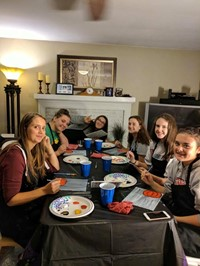 students smile painting pumpkin pictures inside of house