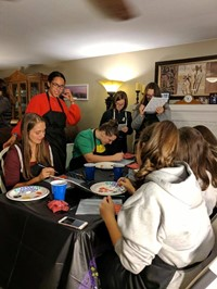 students paint pumpkin pictures inside of house