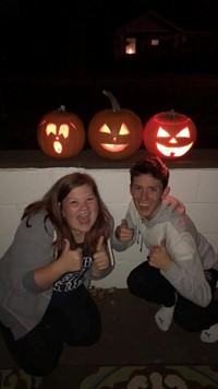students smile in front of pumpkins they carved