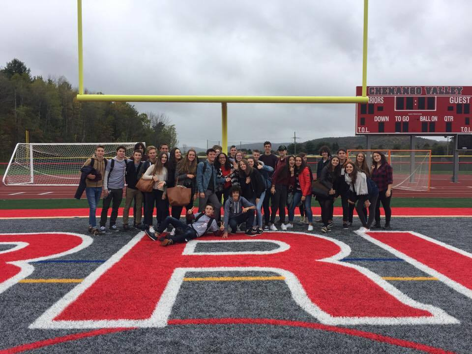 french exchange students as a group on warrior stadium field