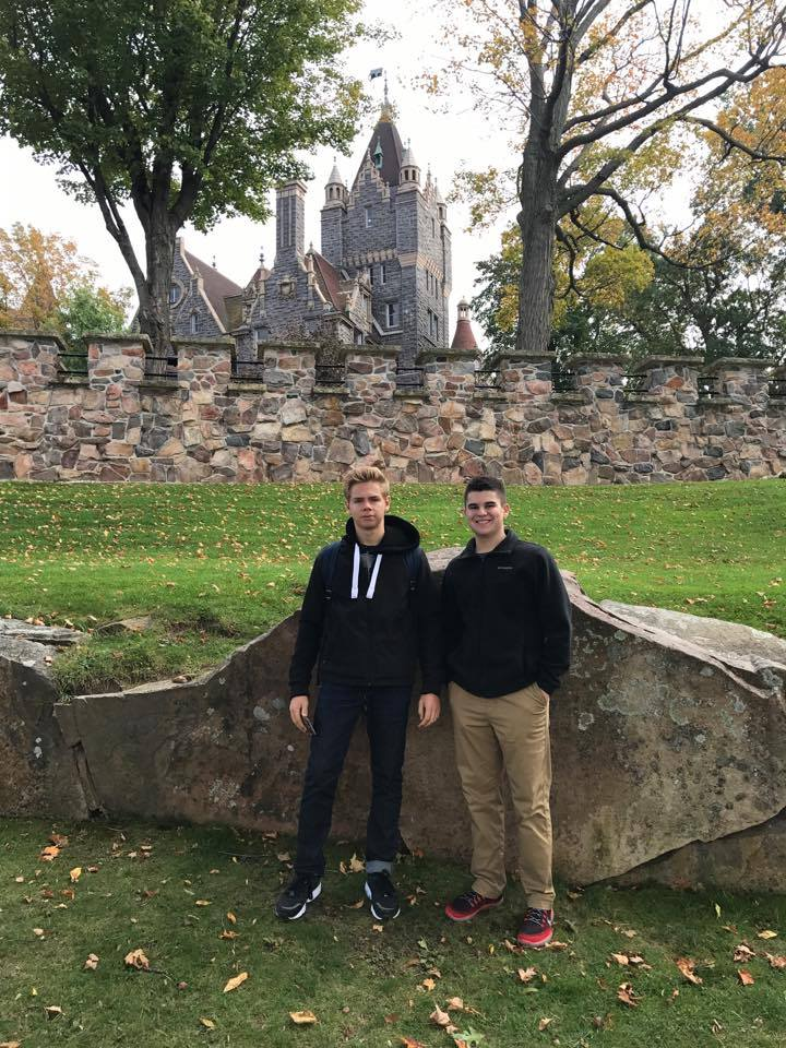 two male students smile standing by rock with large old fashioned building in background