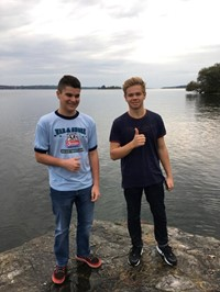 two male students smile standing on rock by water