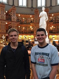 two male students smile inside library