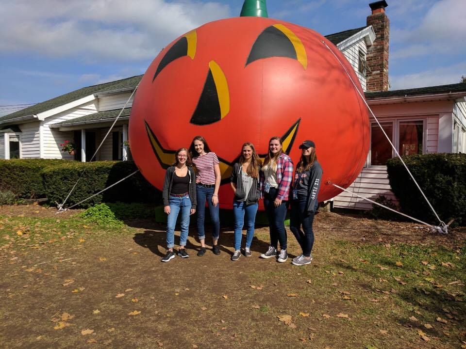 students stand in front of inflatable pumpkin.