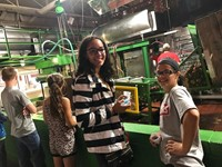 students watch apples getting pressed