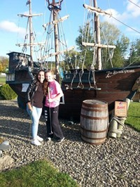 students smile in front of pirate ship