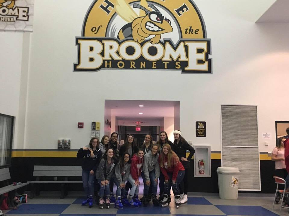 students at suny broome under sign that says home of the broome hornets
