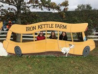 students pose in fake school bus at iron kettle pumpkin farm