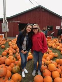 students at iron kettle pumpkin farm by pumpkins