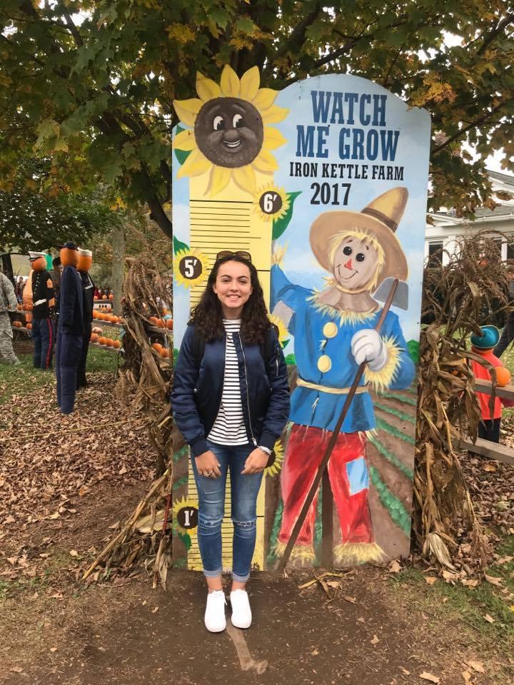 student at growth chart at iron kettle pumpkin farm