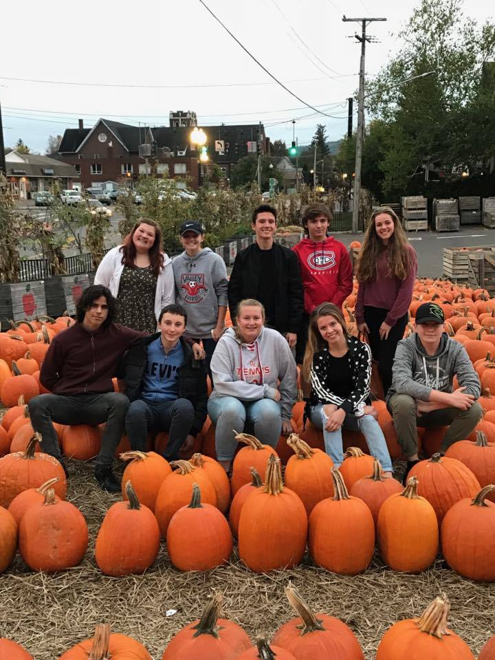 students at the cider mill sitting on pumpkins