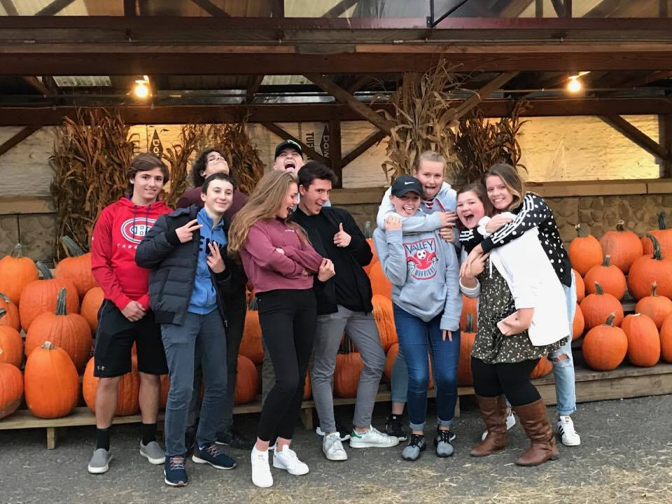 silly photo of group of students standing in front of pumpkins