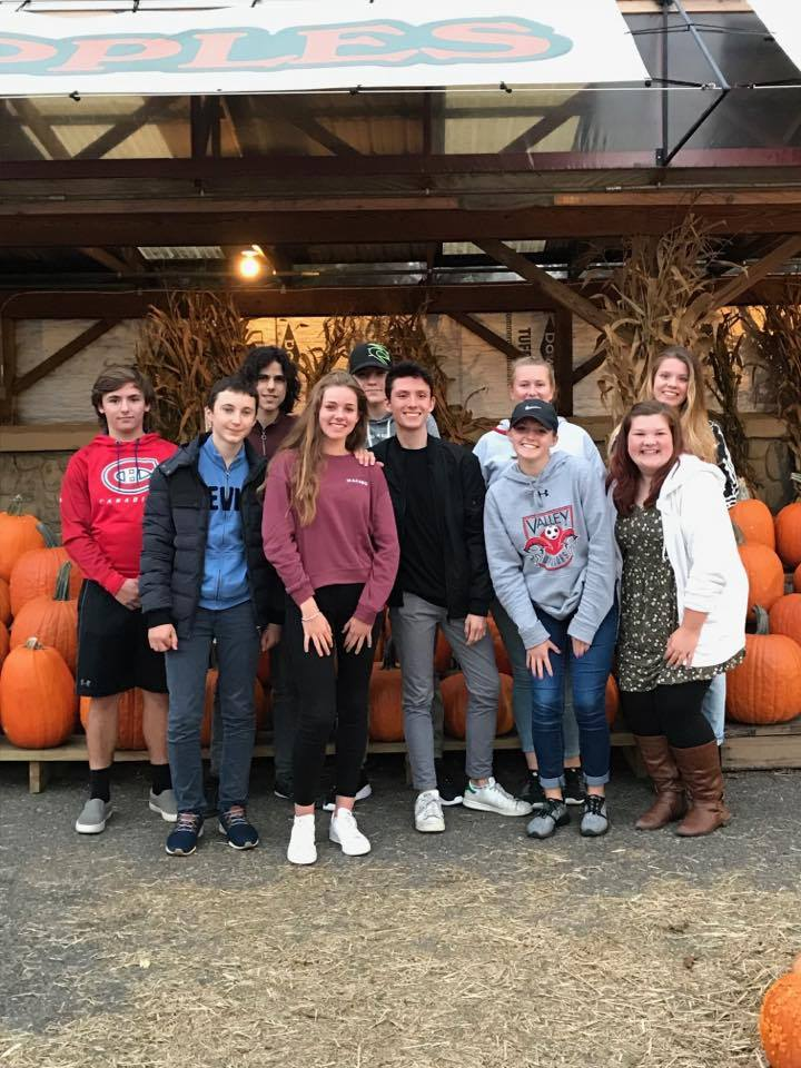 group of students standing in front of pumpkins