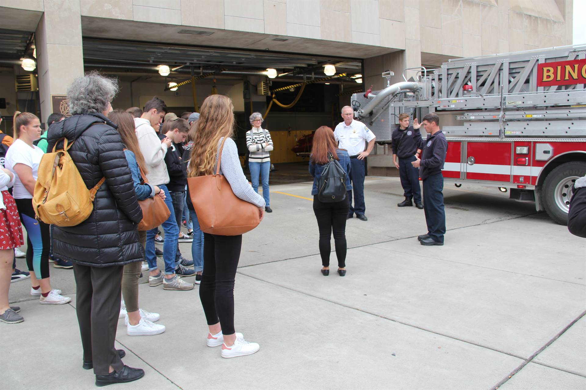 students talking with firemen and fire chief