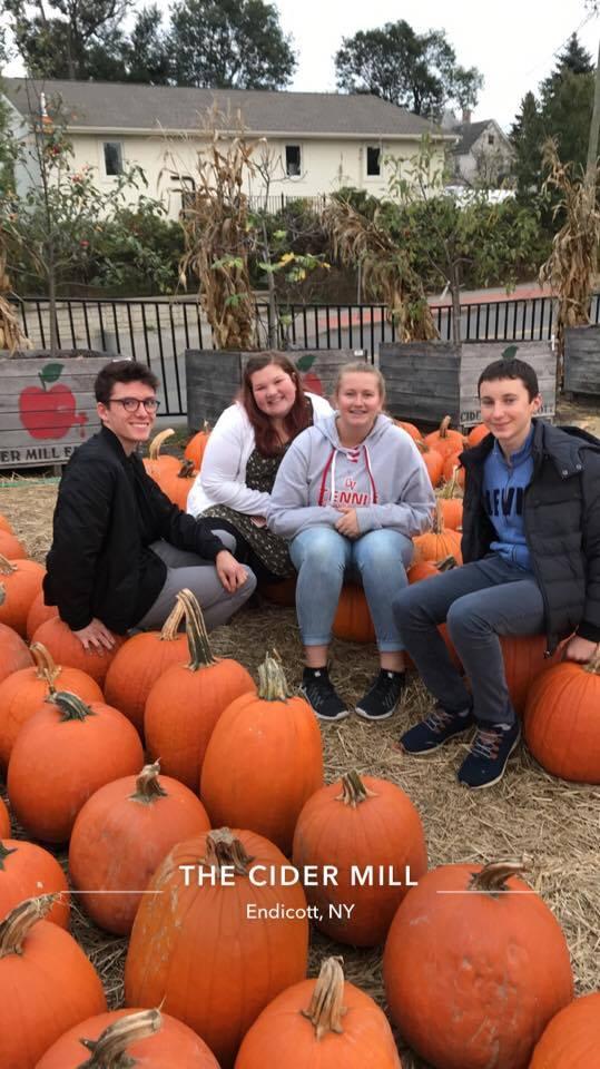 students near pumpkins at cider mill