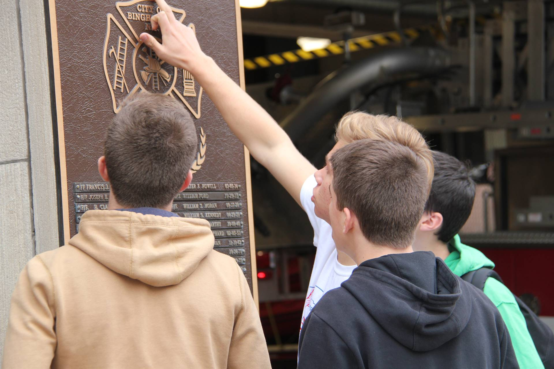 students looking at plaque at binghamton fire department