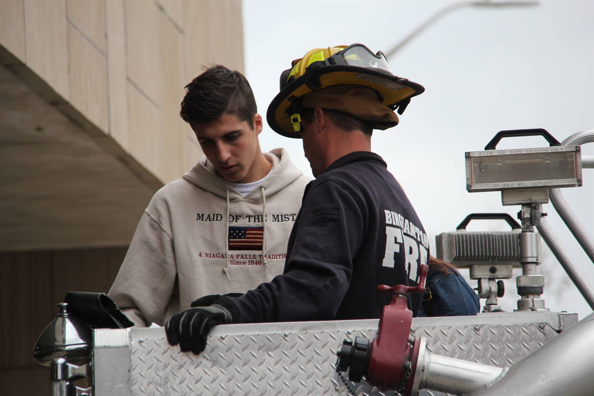 french student inside of bucket on fire truck with fire man