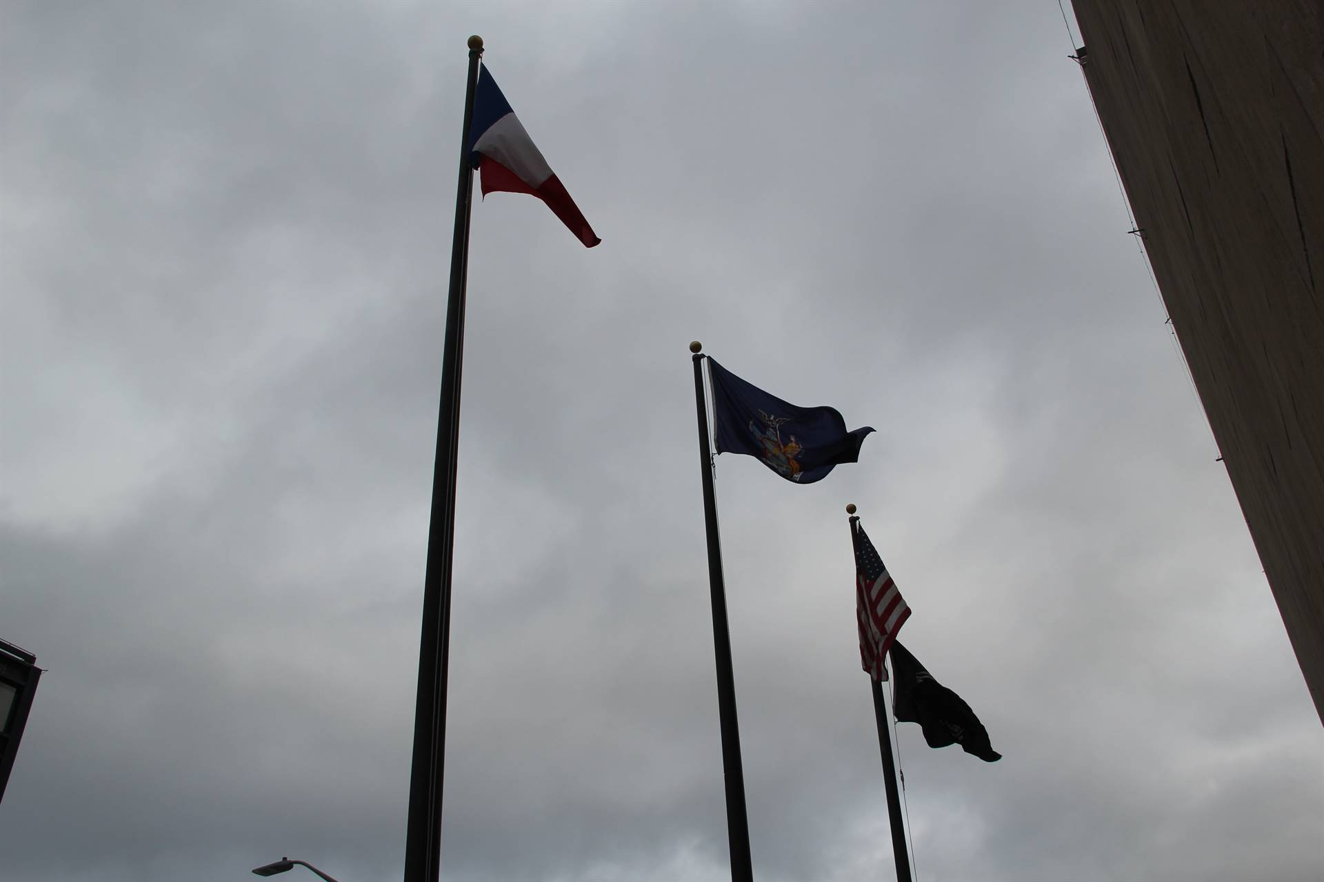 french flag waves with other flags in downtown binghamton outside of city hall