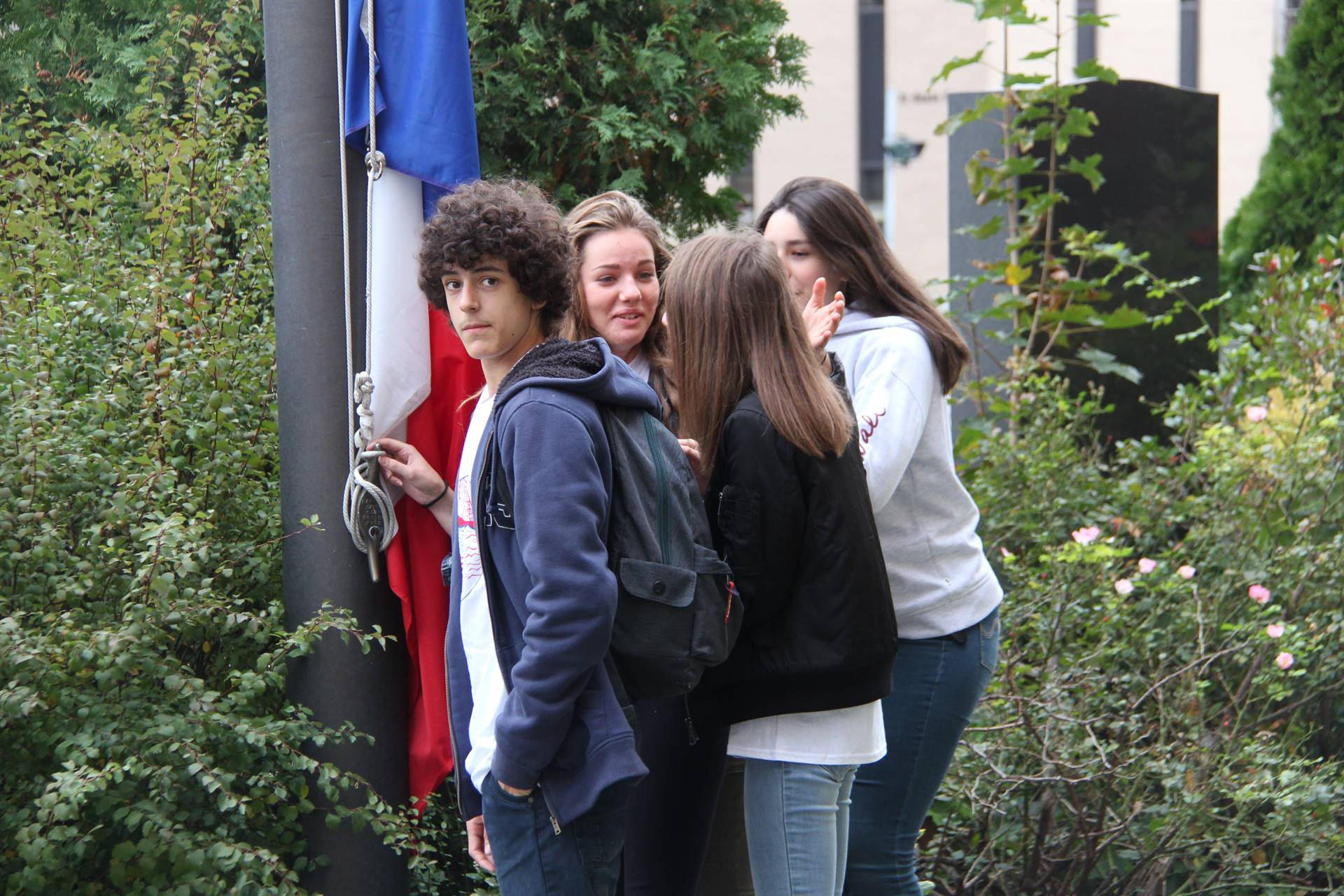 students about to raise france national flag in binghamton