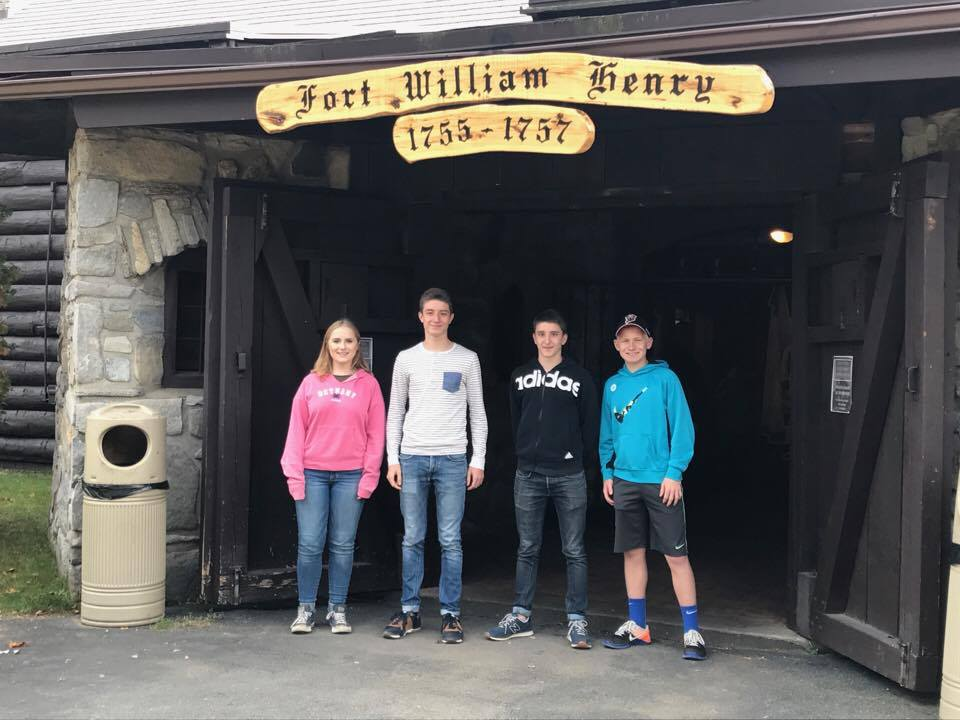 students under sign that reads fort william henry