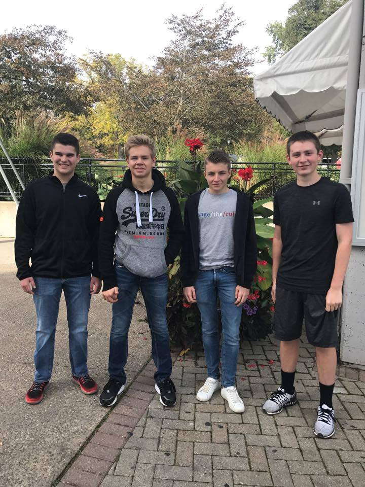 group of four male students outside