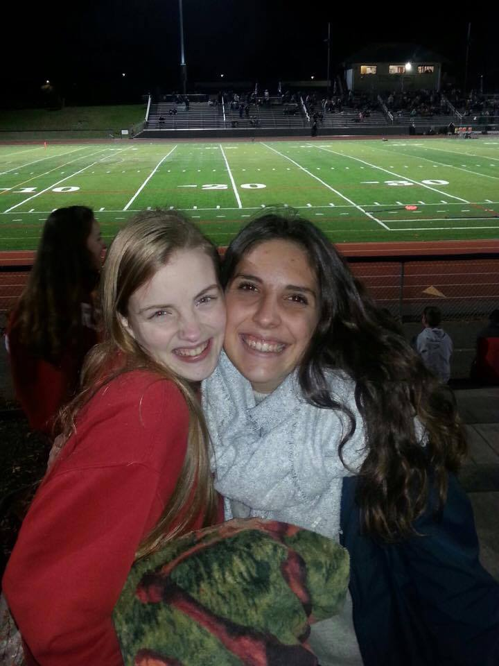 two female students smile at football game